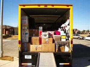rear view of a moving truck with its door open and boxes inside