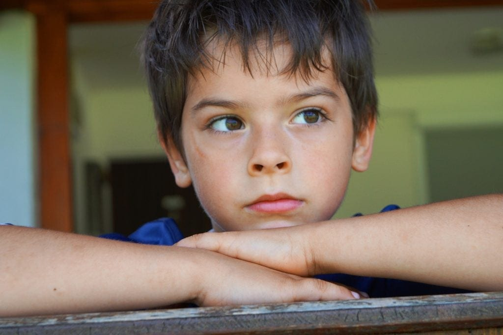 boy looking worried chin on hands
