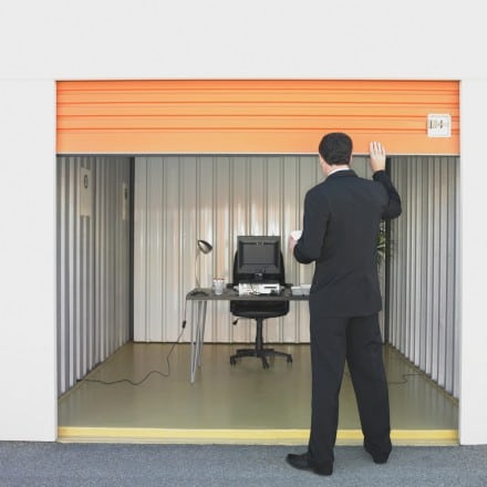 man looking into storage unit seeing a desk and chair