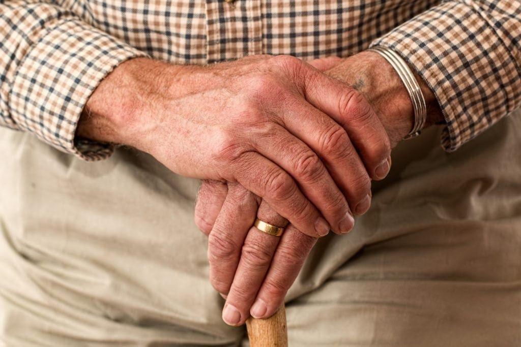 elderly hands folded, holding a cane