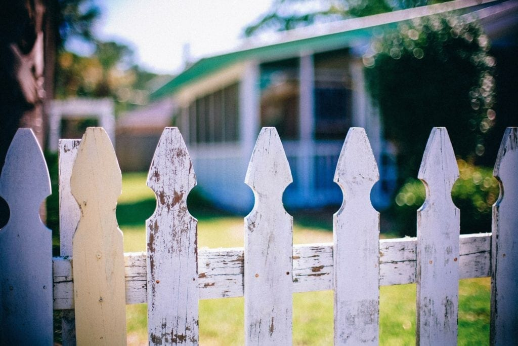 close up of worn picket fence with home in background