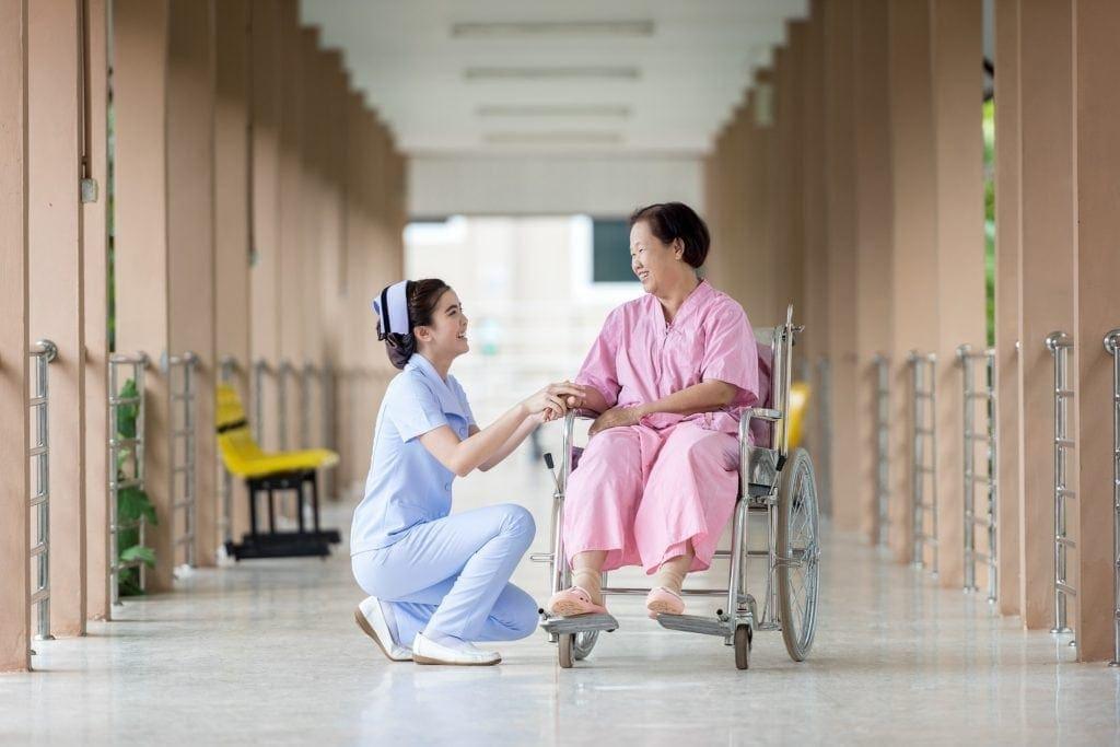 nurse helping senior citizen in wheelchair