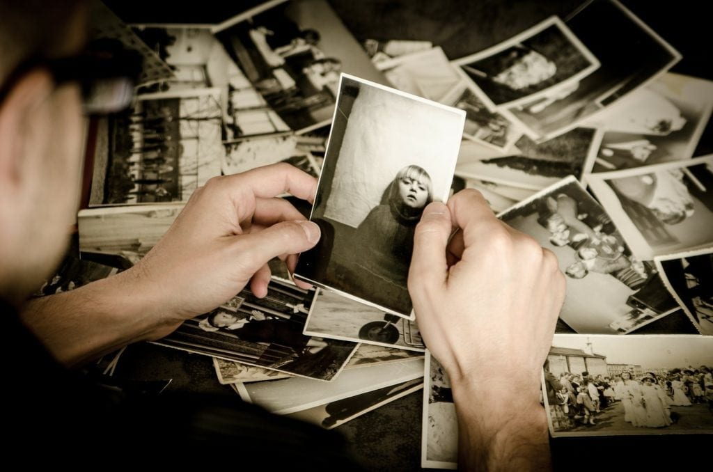 man holding old photo with other old photos on table beneath