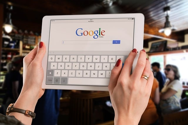 women hands holding tablet with Google Search on screen
