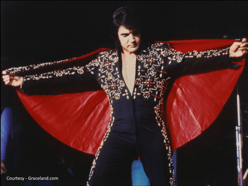 Elvis Presley standing with arms spread wide wearing cape
