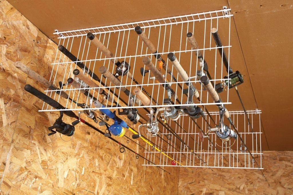 wire racks hanging from ceiling holding fishing rods