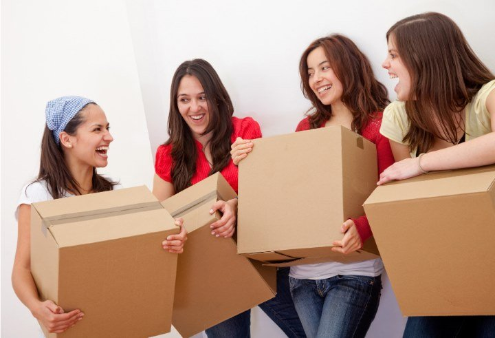 women carrying boxes and laughing