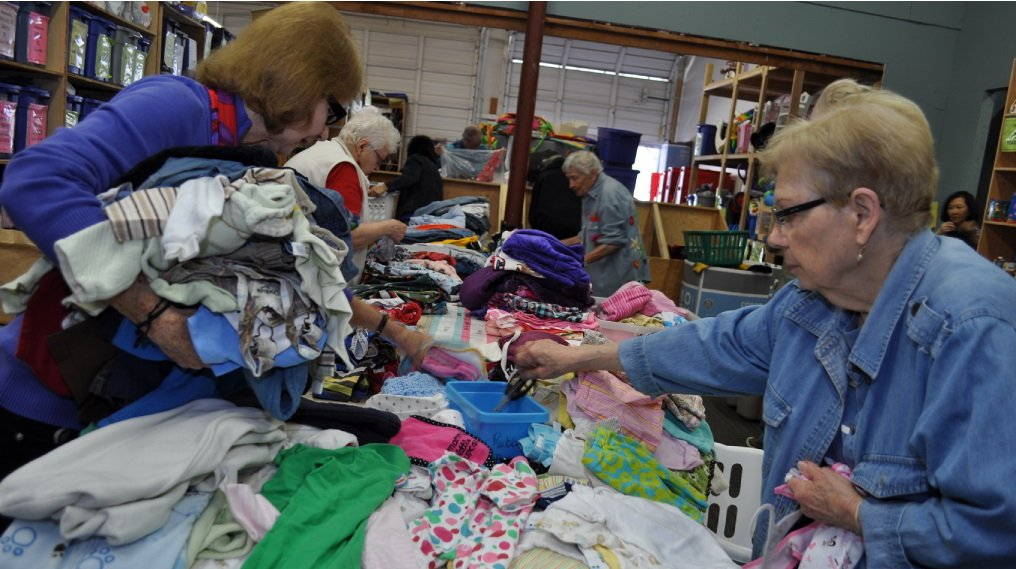 senior women volunteers sorting clothing donations
