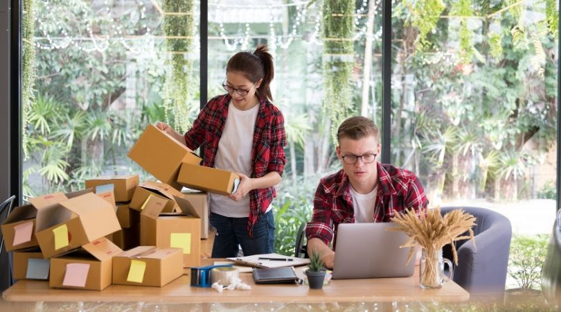 woman sorting boxes and man typing at laptop