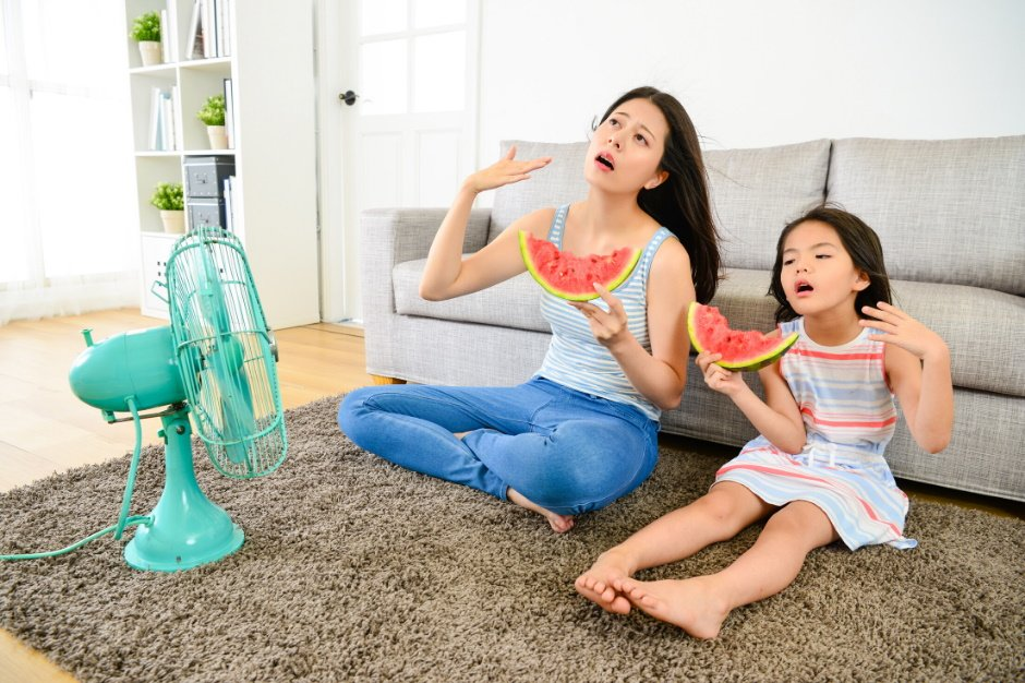 mother and daughter in front of fan acting hot
