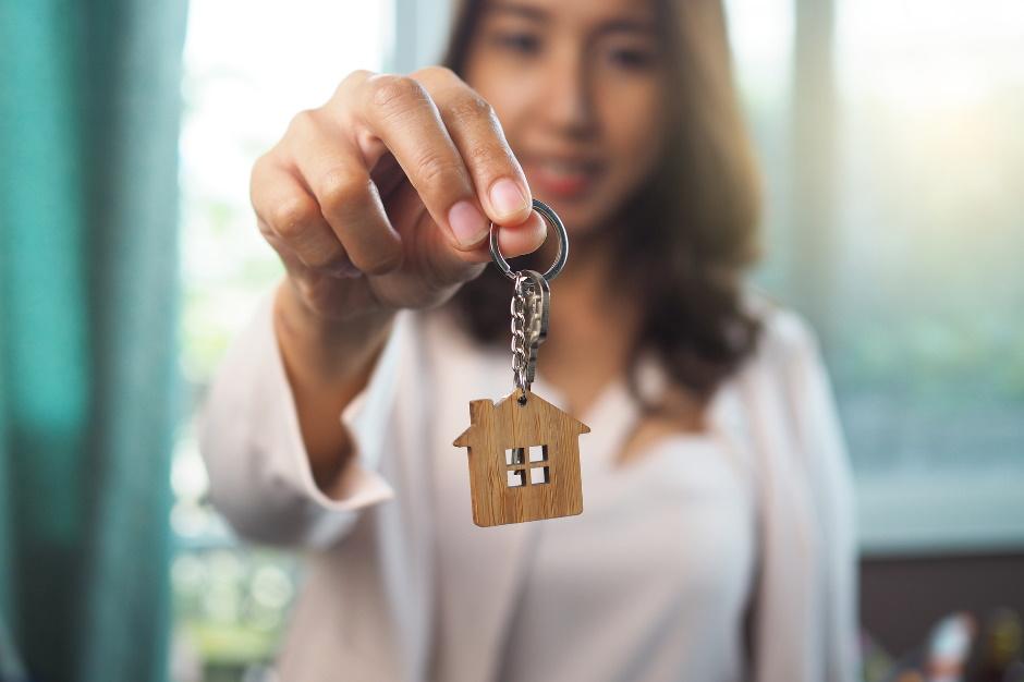 women holding home keychain