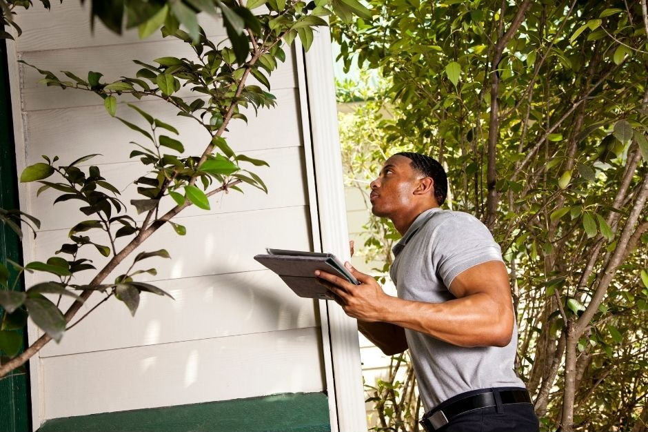 man with clipboard looking at house