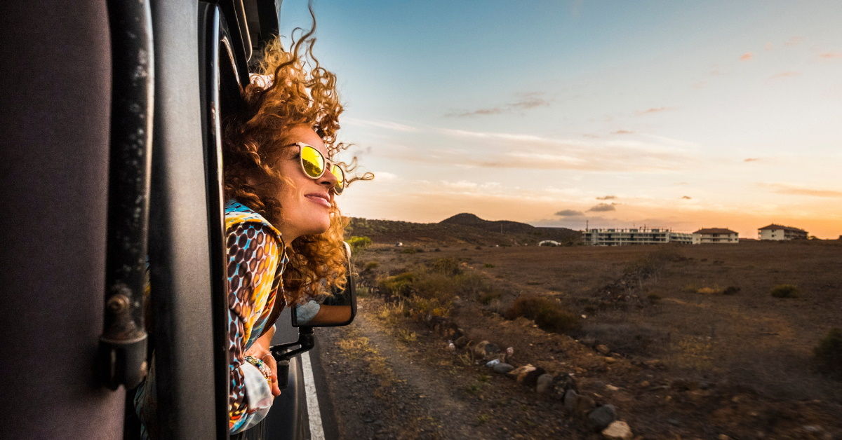 woman with head out of car window